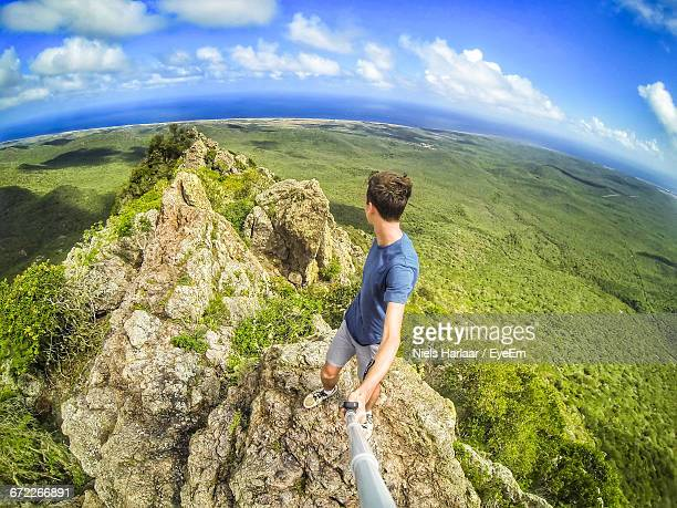young man on the top of a dangerous cliff - danger stock photos and pictures