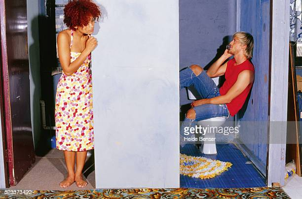 Young man on toilet using mobile phone, woman looking around the corner