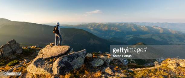young man on top of a mountain watching the sunset - zen like stock pictures, royalty-free photos & images