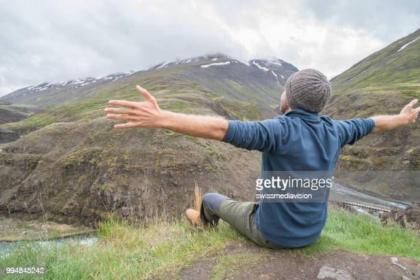 Young man on top of canyon arms outstretched for happiness