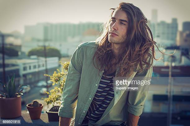 young man on urban rooftop - langes haar stock-fotos und bilder