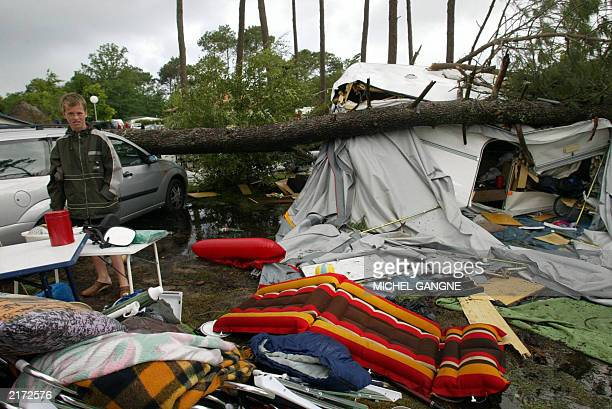 A young man on vacation stands 16 July 2003 in the devastated camping de la Rive in Biscarrosse southwestern France following the violent storm that...