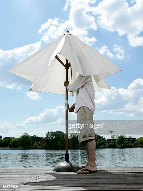 A young man opening a patio umbrella on a jetty