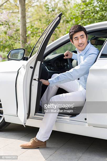 Young man opening car door