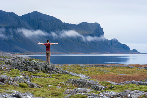 Young man opening his arms wide looking at rugged coastline of Hringvegur, East Iceland, Iceland - gettyimageskorea