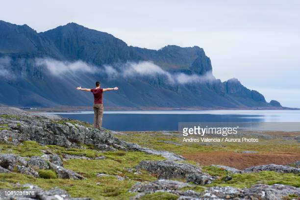 Young man opening his arms wide looking at rugged coastline of Hringvegur, East Iceland, Iceland