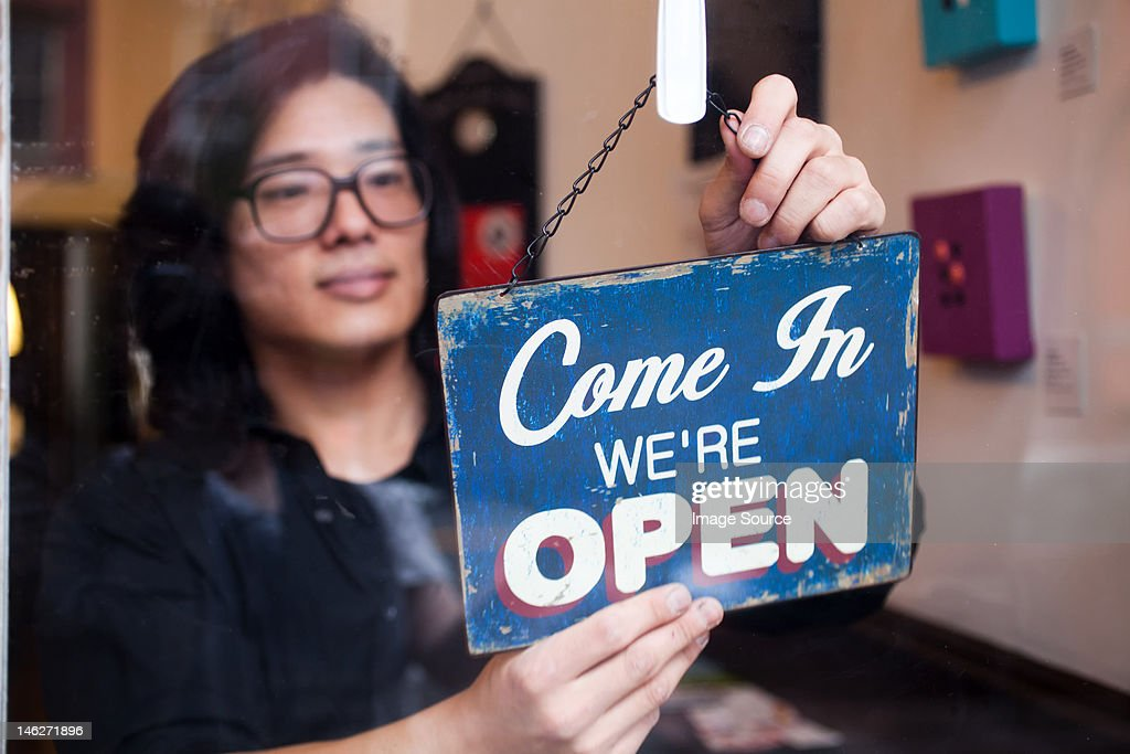 Young man opening shop : Stock Photo