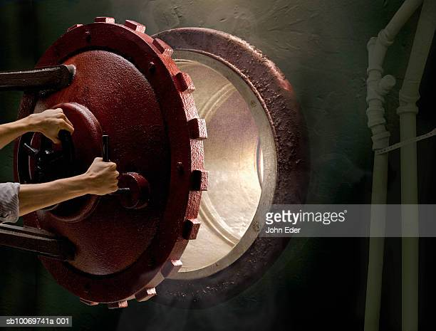 Young man opening steel hatch set in wall