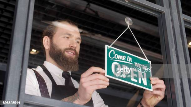 young man opening the shop - open for business stock pictures, royalty-free photos & images