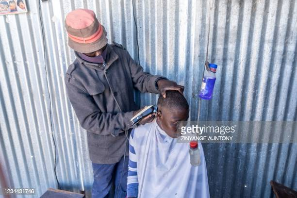 Young man operates a barber shop with sanitisers in place as per requirement of COVID-19 regulations on 3 August 2021, in Cowdray Park township,...