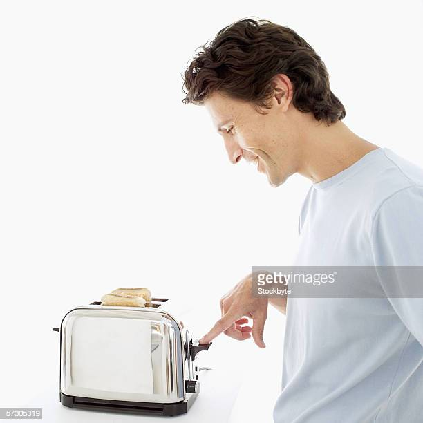 Young man operating an electric bread toaster