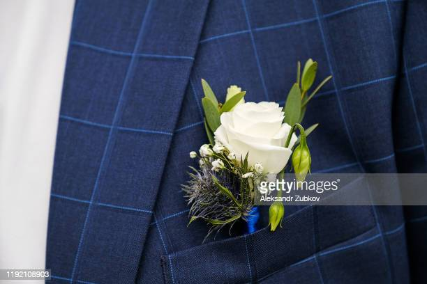 a young man or groom in a white shirt, bow tie and blue checked vest or jacket. beautiful boutonniere of white roses and green leaves in a vest pocket or lapel. wedding theme. - giacca da abito foto e immagini stock