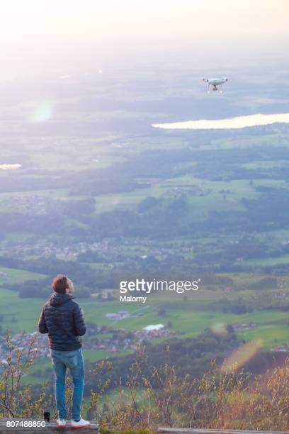 Young man or pilot with a remote control flying a drone