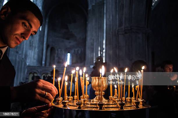 Young man, orthodox christian, lighting candles inside Svetitskhoveli cathedral, most venerated places of worship for Georgian Orthodox Christians,...