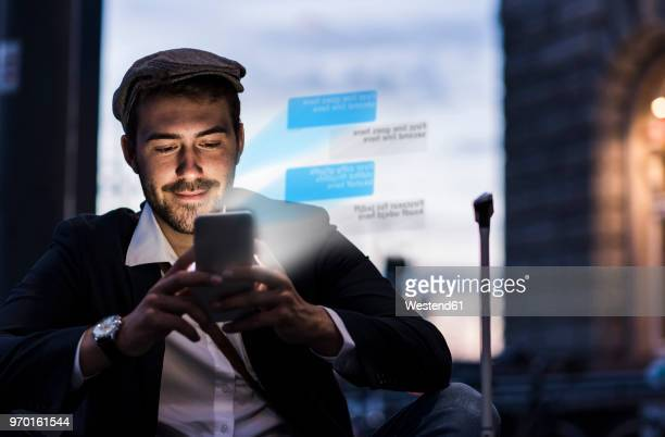 young man outdoors at dusk with text emerging from smartphone - caucasian appearance stock pictures, royalty-free photos & images