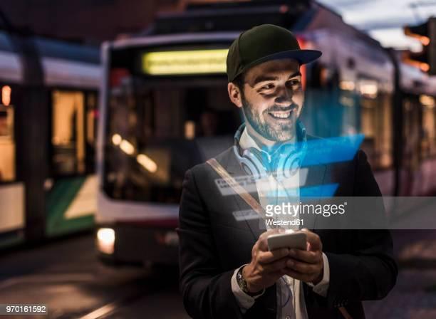 young man outdoors at dusk with text emerging from smartphone - fortschritt stock-fotos und bilder