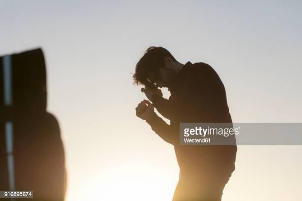 Young man outdoors at sunset