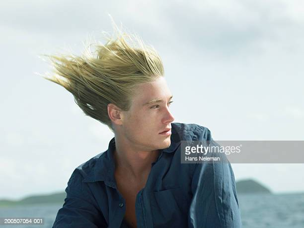 Young man outdoors, hair blowing in wind