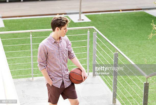 Young man outdoors, holding basketball