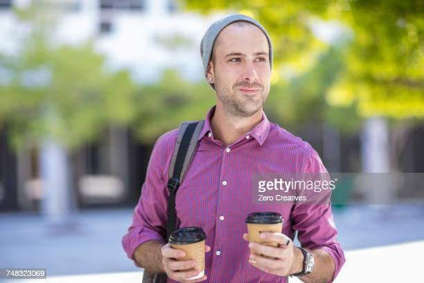 young man outdoors, holding two takeaway coffee cups - dois objetos - fotografias e filmes do acervo