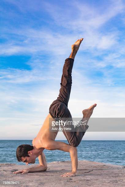 young man outdoors, in yoga position, balancing on hand and forearm - hands in her pants fotografías e imágenes de stock