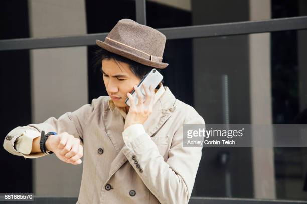 Young man outdoors, using smartphone, looking at wristwatch