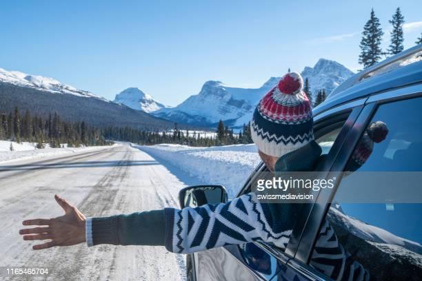 雪山道のロードトリップで若い男が車の中から腕を伸ばす - 防寒着 ストックフォトと画像