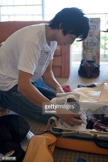 Young man packing clothing
