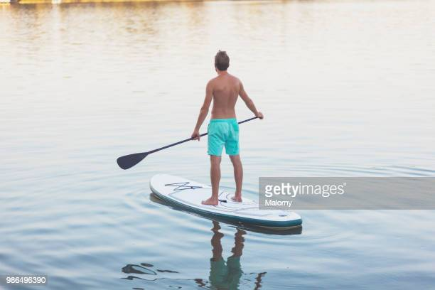young man paddle boarding on lake chiemsee. chiemsee, chiemgau, bavaria, germany - paddleboard stock pictures, royalty-free photos & images