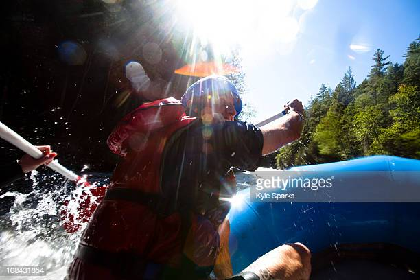 A young man paddles down a river while whitewater rafting.