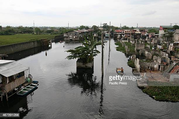 MALABON MANILA PHILIPPINES A young man paddles his way through the flooded community Around 175 families live in Artex Compound in Malabon The...