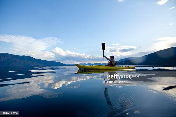 young man paddles yellow kayak on lake. - kayaking stock pictures, royalty-free photos & images