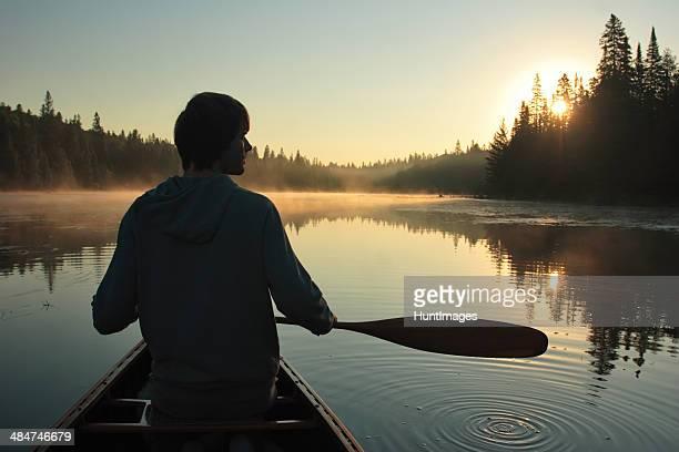 Young man paddling a canoe at sunset
