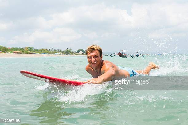 Young Man Paddling a Surfboard Surfing
