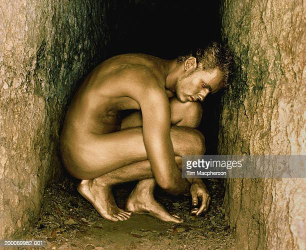 Young man painted gold, crouching in rock crevice