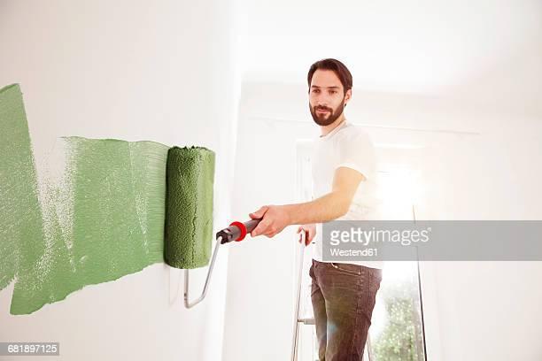 young man painting a wall green - malen stock-fotos und bilder
