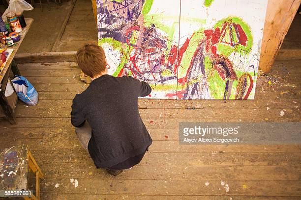 Young man painting on canvas in studio