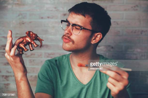 young man painting plastic elephant figure with copper paint - freizeit stock-fotos und bilder