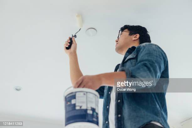 young man painting the ceiling with a paint roller at home - painting stock pictures, royalty-free photos & images