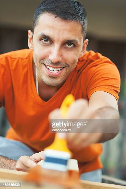 Young man painting the fence and smiling for camera