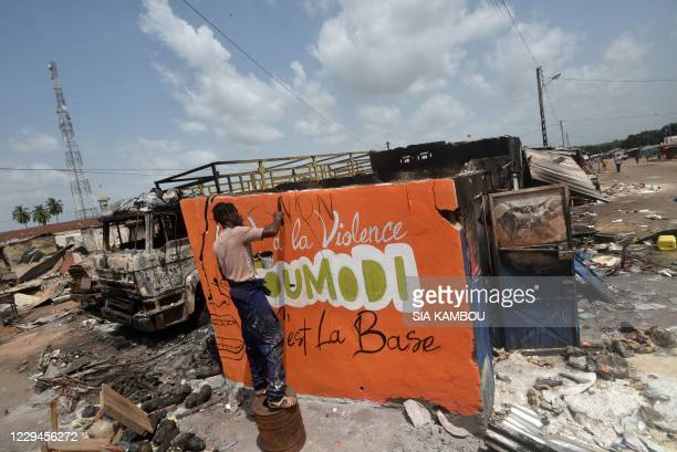 """Young man paints a sign on a wall of a damaged shop that reads: """"no to violence, Toumodi is the basis"""" in the market of Toumodi on November 4 during..."""