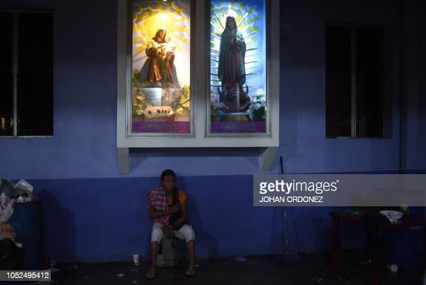 TOPSHOT A young man part of a group of Honduran migrants heading in a caravan to the United States rests at 'Tres Caidas Church' in Tecun Uman on the...