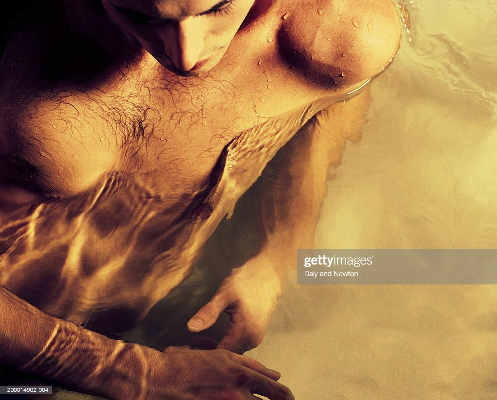 Young man partially submerged in water, close-up, elevated view : Stock Photo