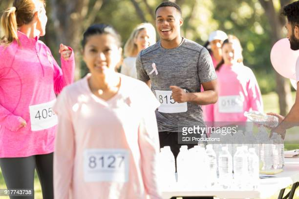 young man participates in race for the cure of breast cancer - social awareness symbol stock photos and pictures