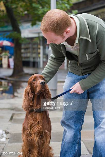 Young man patting red-setter dog