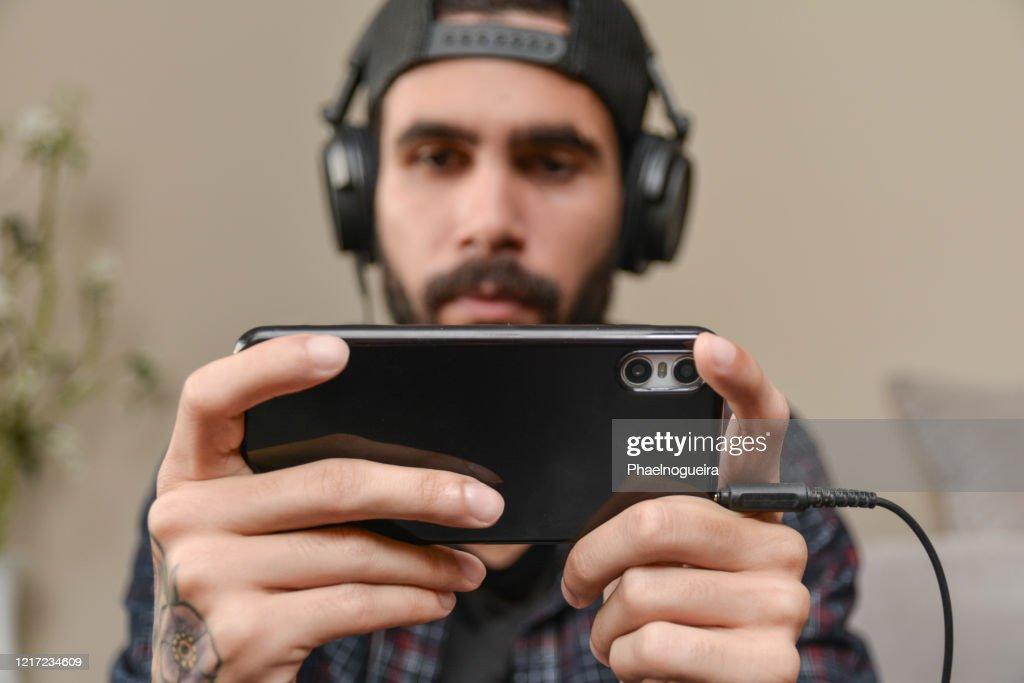 Junger Mann bezahlt ein mobiles Spiel zu Hause. Smartphone-Gaming : Stock-Foto