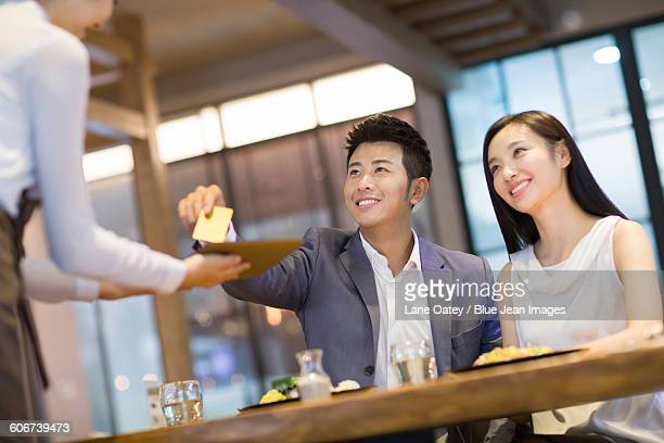 Young man paying bill by credit card in restaurant