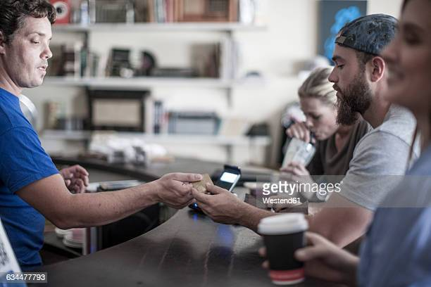 Young man paying with credit card at coffee shop