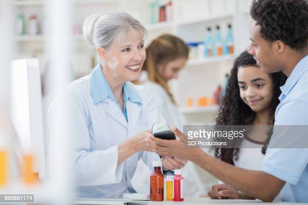 Young man pays for pharmacy purchase with mobile app