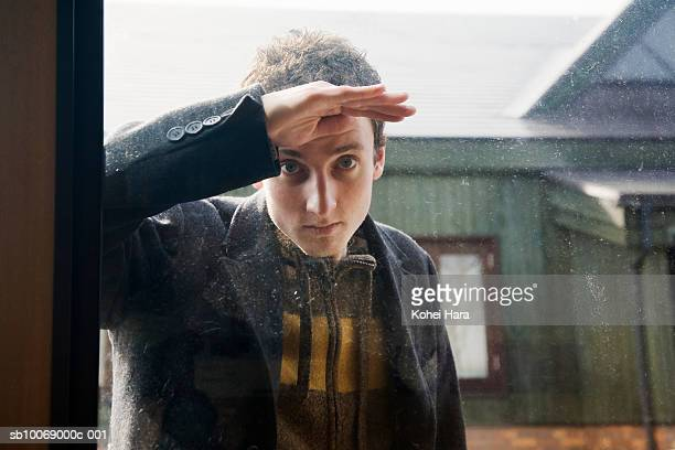 young man peeking trough window, portrait - trough stock photos and pictures